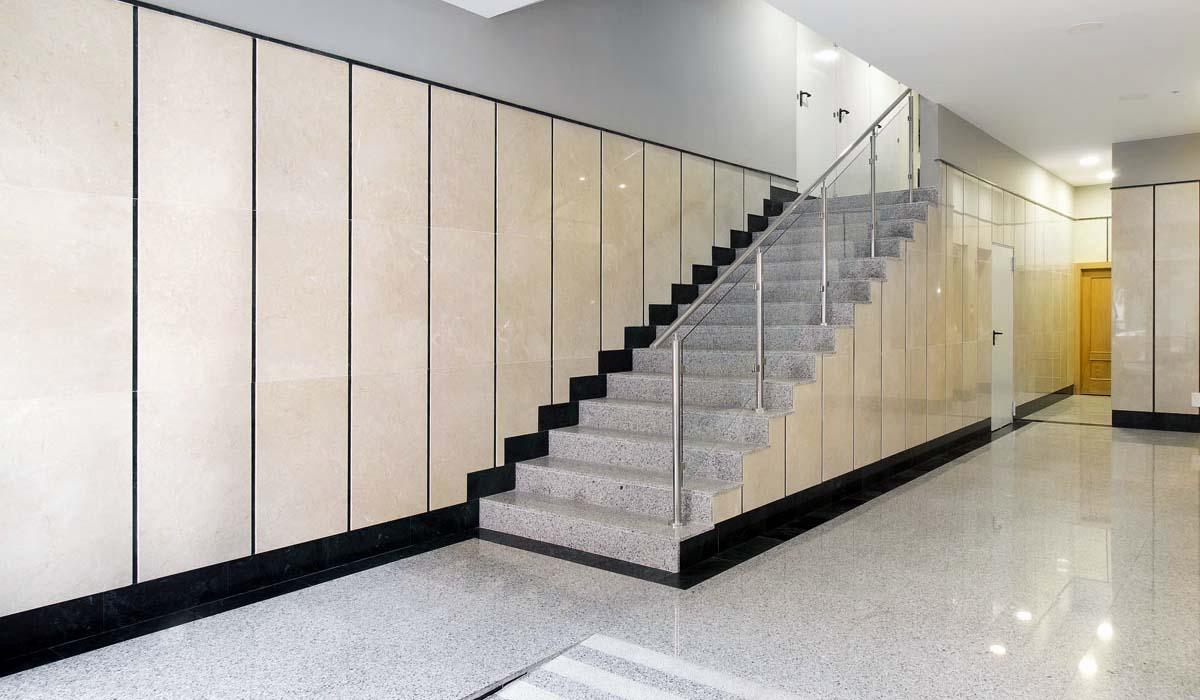 Portal reformado amplio y luminoso con rampa y escalera para mejorar la accesibilidad al edificio